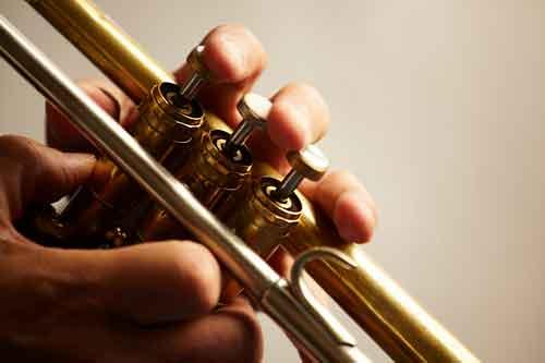 Manos tocando una trompeta