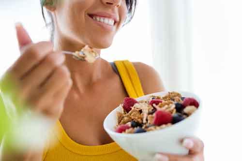 Mujer comiendo cereales con leche