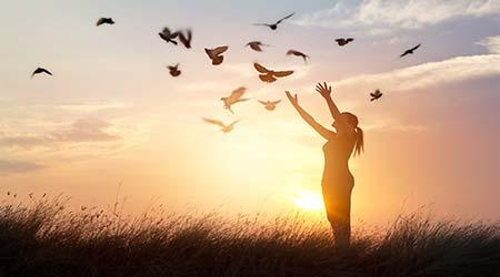 Mujer con palomas volando alrededor