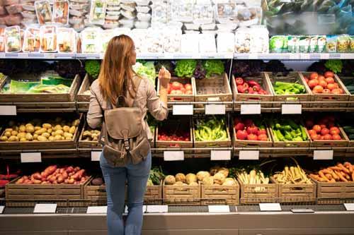 Mujer escogiendo variedad de fruta en frutería