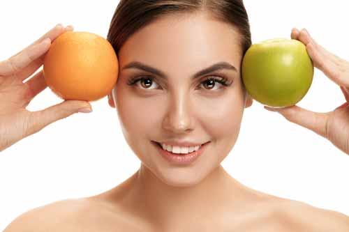 Mujer hermosa sosteniendo naranja y manzana