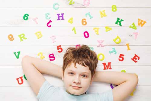 Niño tumbado sobre letras y números