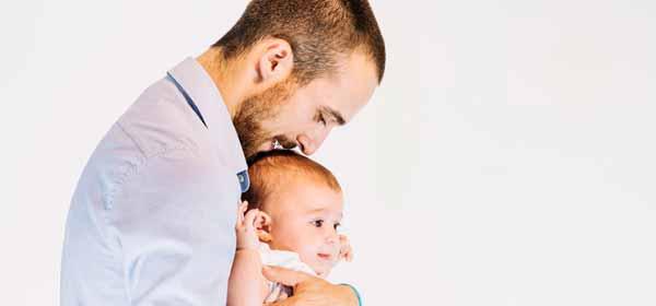 Padre cariñoso con bebé en brazos