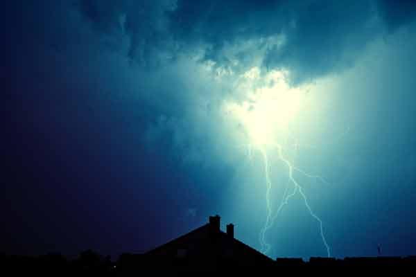 Rayo en tormenta golpeando una casa