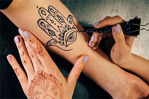 Tatuaje de mano con ojo en brazo